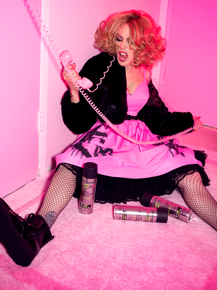 In an all pink inspired room, Micheline Pitt screams into the receiver of a rotary phone while wearing the Miss Kitty 9 Lives Dress in Pink Spray Paint Print while also sporting fishnet stockings and black vinyl boots.