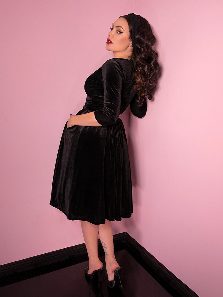 Shot of the back of the Allure Dress in Black Velvet being worn by Micheline Pitt, owner and model of Vixen Clothing.