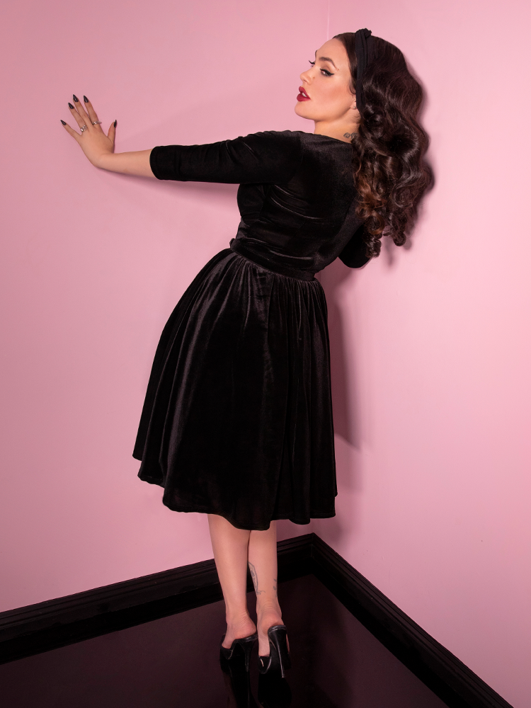 Back shot of Micheline Pitt with her left arm outstretched and pressed against the wall while she models the Allure Dress in Black Velvet from Vixen Clothing.