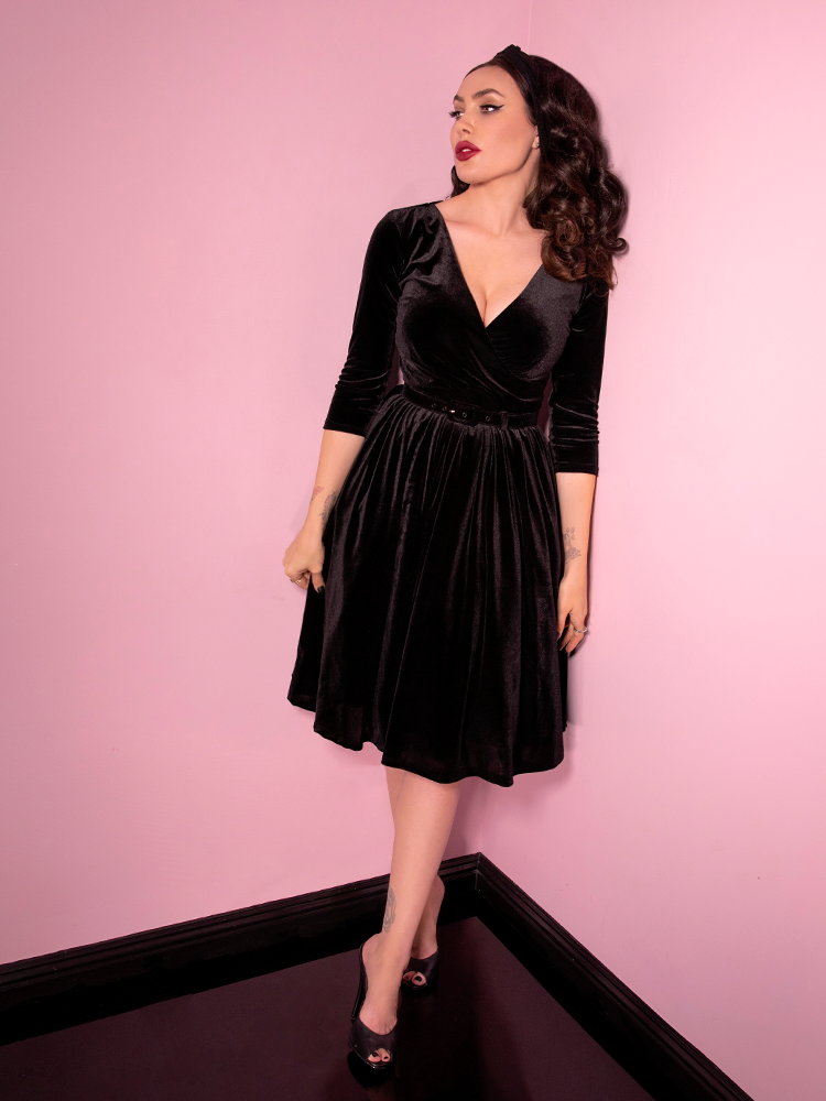Looking off to the side, Micheline Pitt models the Allure Dress in Black Velvet from Vixen Clothing - the finest vintage and retro style clothing manufacturer and retailer.