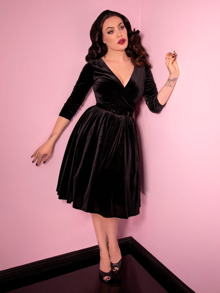 Posed like a life size doll, Micheline Pitt shows off the Allure Dress in Black Velvet with her arms extended out and posed in different positions.