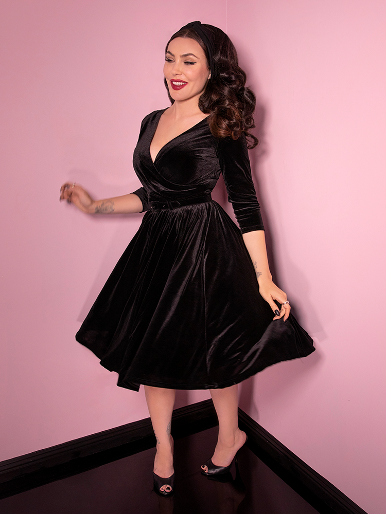 Action shot of Micheline Pitt twirling around in the Allure Dress in Black Velvet with black heel shoes.