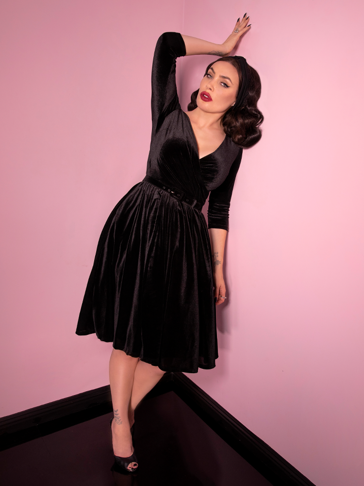 Leaning with her left shoulder into the wall, Micheline Pitt looks directly into the camera with a piercing glare while wearing a vintage inspired black velvet dress from Vixen Clothing.