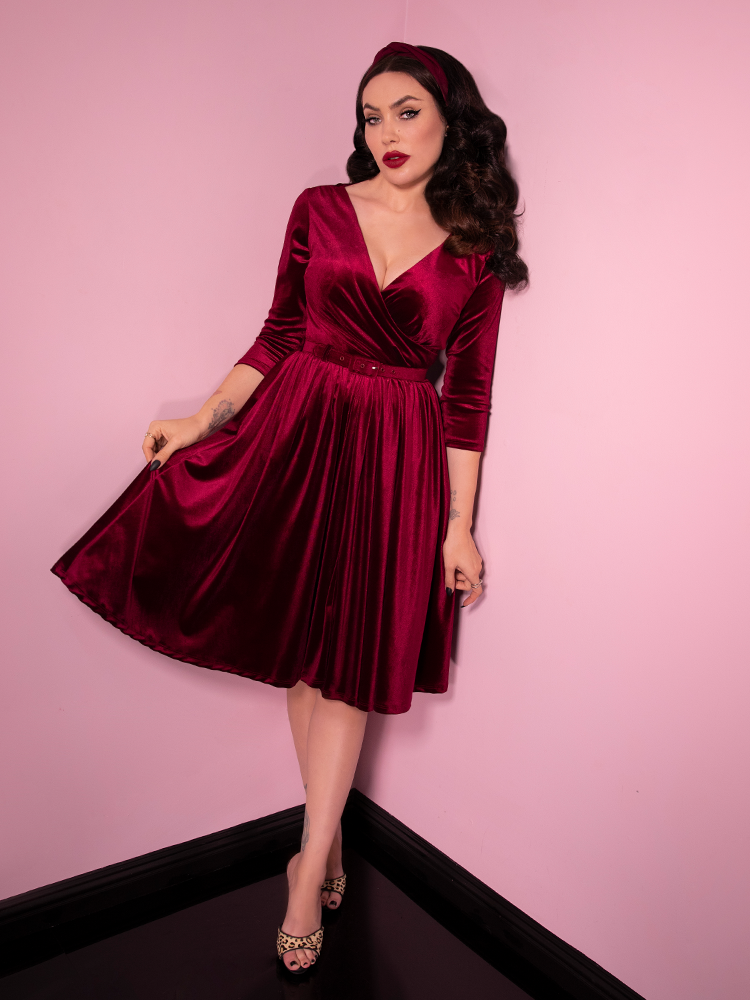 Staring directly into the lens of the camera while pulling out one side of the skirt on her dress, Micheline Pitt looks devilishly divine in the newest vintage dress release from Vixen Clothing.