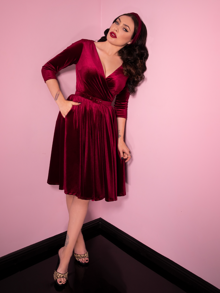 With one shoulder braced against the walls of her Burbank, CA shop, Micheline Pitt models the Allure Dress in Raspberry Red Velvet