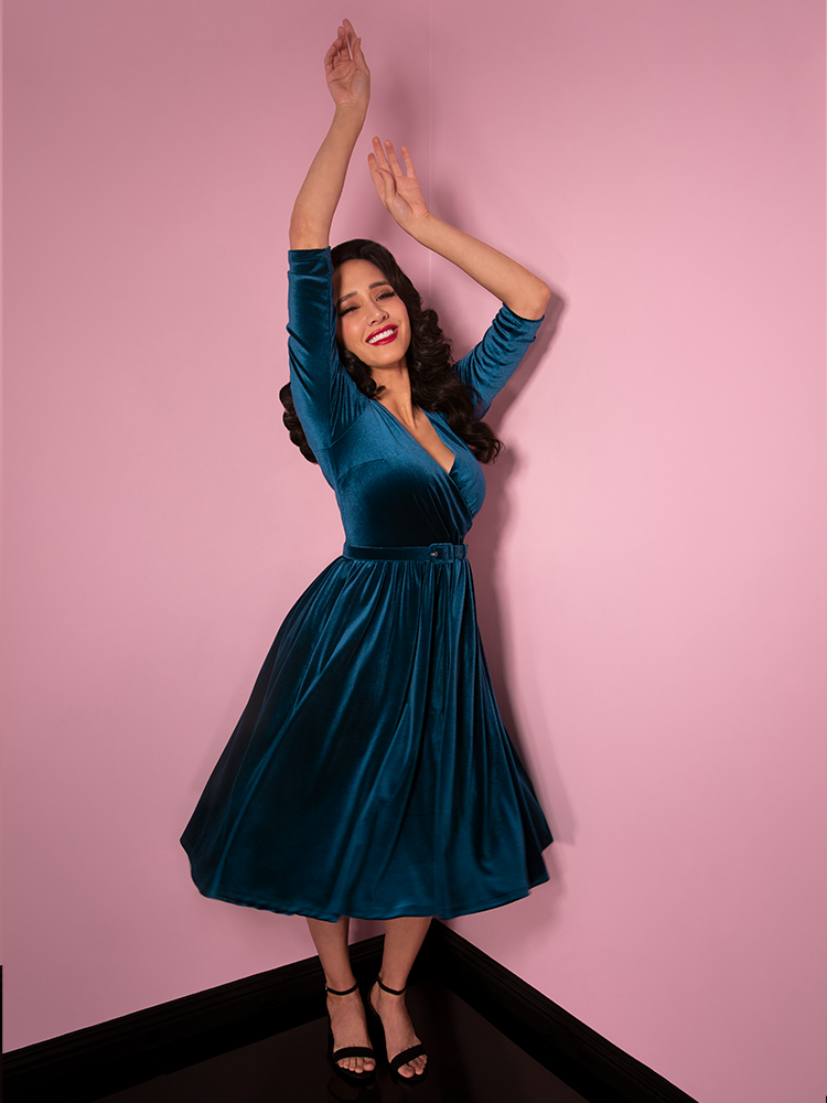 Full body shot of Milynn Moon playfully dancing around with her arms raised in the air, Milynn Moon sports the newest retro dress offering from Vixen Clothing - the Allure Dress in Teal Velvet.