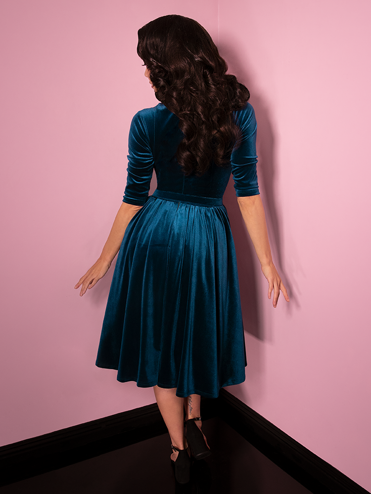 Facing away from the camera, model Milynn Moon subtly has her fingers fanned out while her arms are lowered by her side. She is wearing the Allure Dress in Teal Velvet from Vixen Clothing.