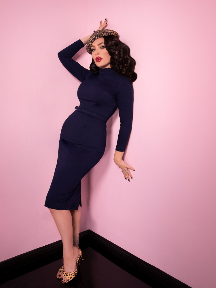 Leaning against pink walls while bracing herself with her arms, Micheline Pitt wears the Bad Girl Wiggle Dress in Navy with a leopard beret