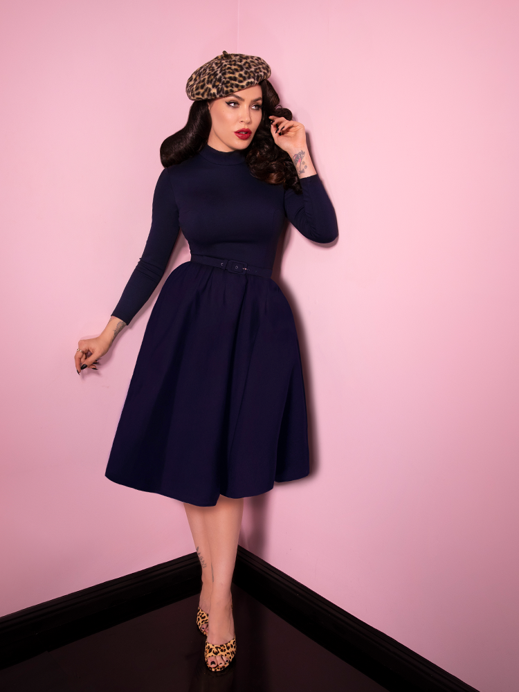 Captured mid-stride, Micheline Pitt wears the Bad Girl Swing Dress in Navy from Vixen Clothing - the newest retro inspired dress from this vintage clothing house.