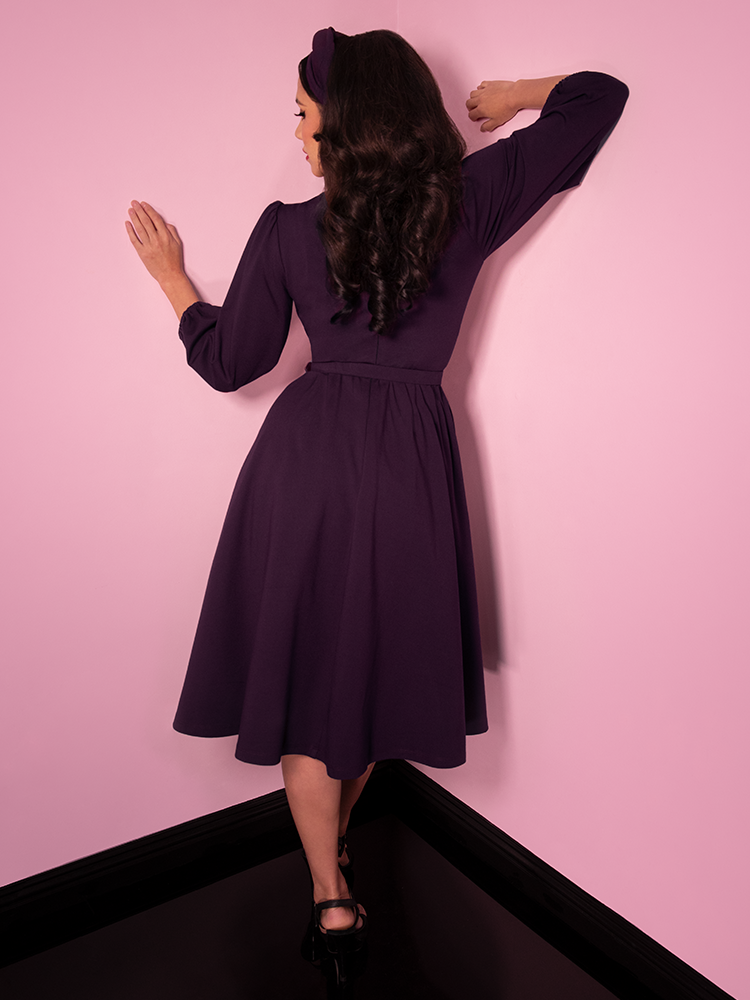 Back shot of Milynn Moon modeling the Bawdy Swing Dress in Eggplant from Vixen Clothing.
