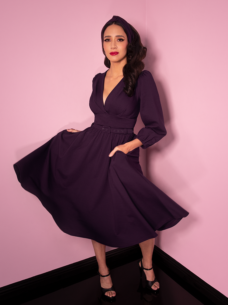 Milynn Moon photographed mid-twirl wearing the Bawdy Swing Dress in Eggplant from Vixen Clothing.