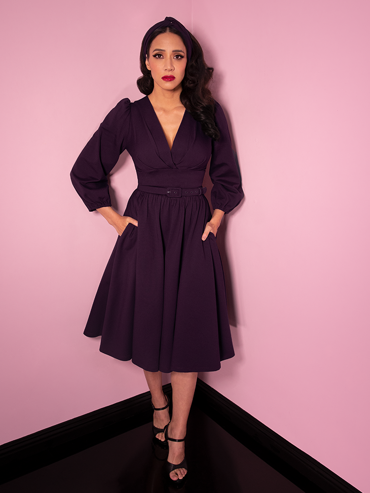 Milynn Moon staring with a serious look on her face shows off the Bawdy Swing Dress in Eggplant color.