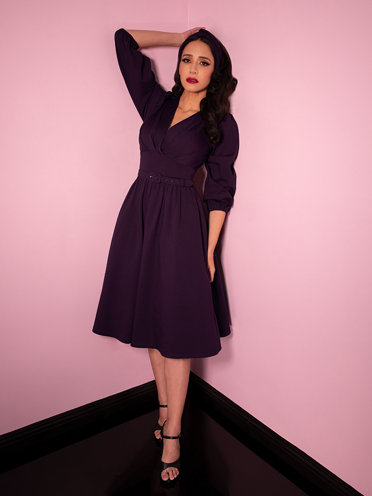 Full body length shot of Milynn Moon in the vintage inspired Bawdy Swing Dress in Eggplant. Made by retro clothing retailer Vixen Clothing.