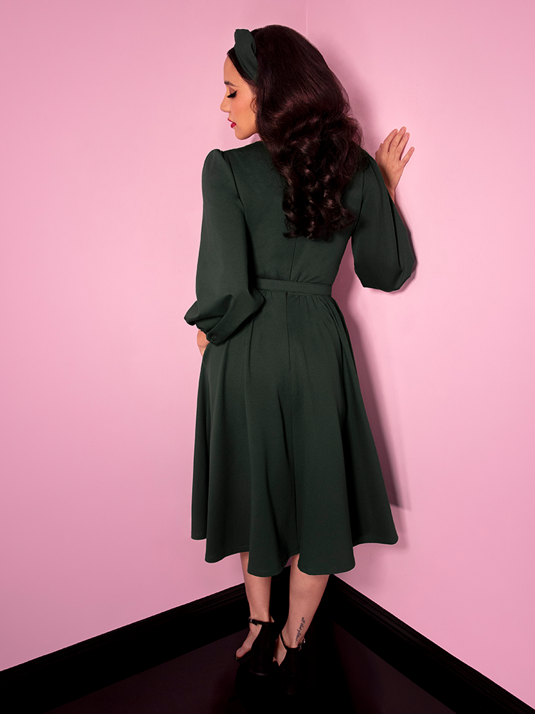 Milynn Moon showing off the back of the Bawdy Swing Dress in Hunter Green from retro dress maker Vixen Clothing.