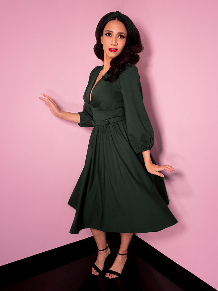 Posing and showing the camera a slight smirk, Milynn Moon is photographed in the Bawdy Swing Dress in Hunter Green.