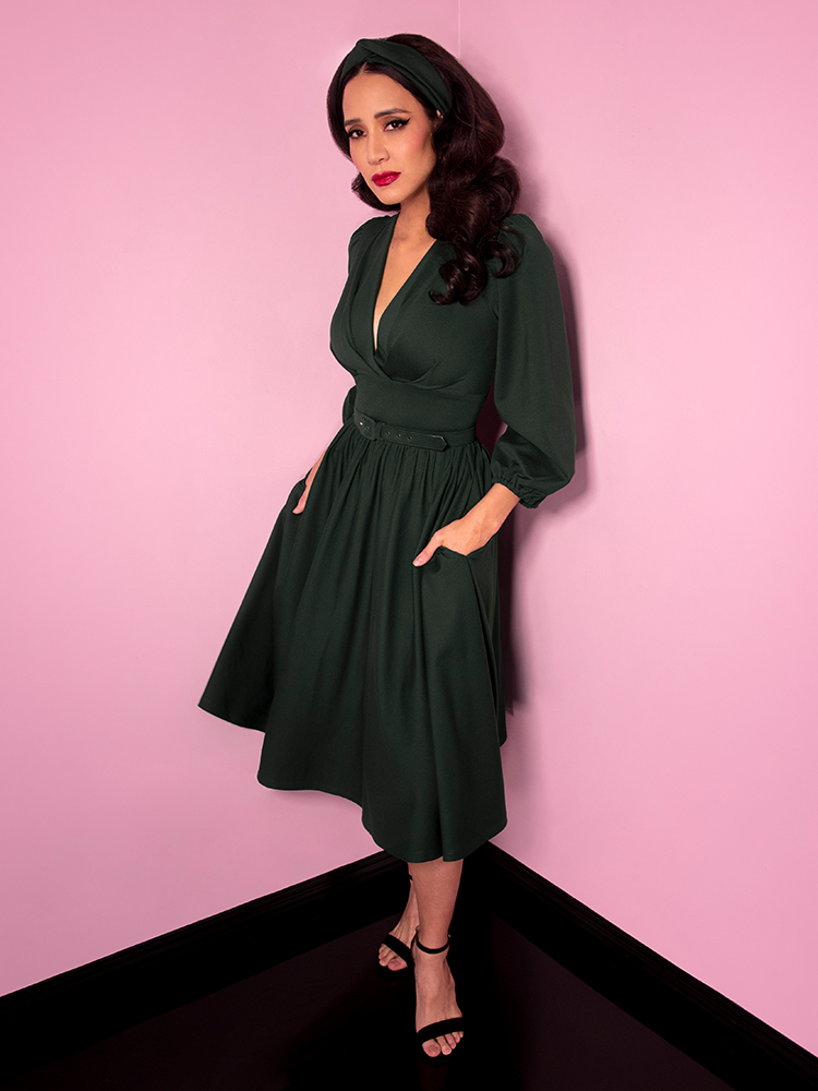 Milynn Moon photographed wearing the Bawdy Swing Dress in Hunter Green with her hands tucked into the pockets.