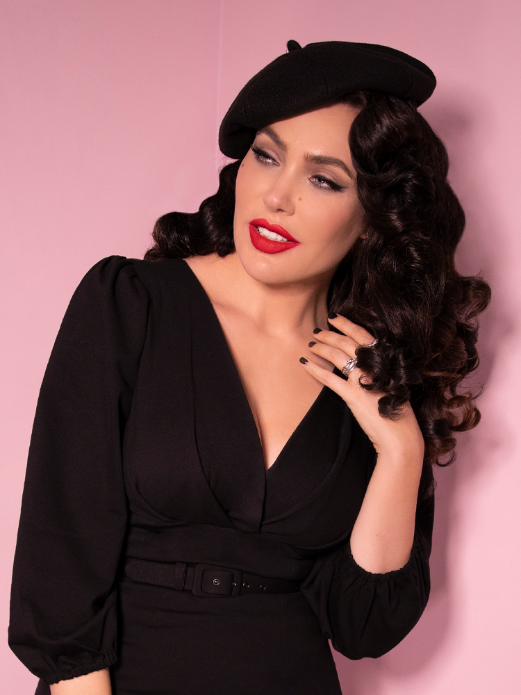 Micheline Pitt smiling and looking off-camera while modeling an all-black outfit including the Starlet Beret in Black.