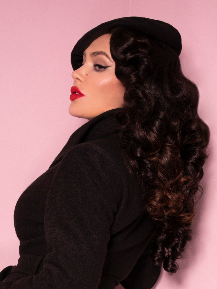 Profile shot of Micheline Pitt wearing an all black vintage inspired outfit including the Starlet Beret in Black from Vixen Clothing.