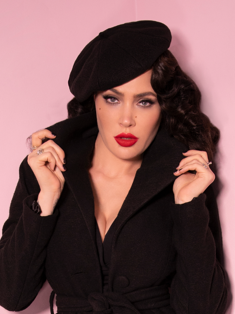 Looking directly into the camera while flipping her collar up models the Starlet Beret in Black.