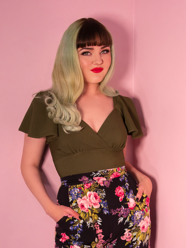 Model posing with her hands in her pockets, wearing black vintage vacation floral pants and green babydoll top