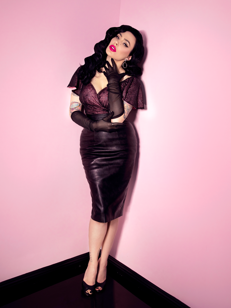 Full-length shot of Micheline Pitt wearing the Babydoll Crop Top in Pink with Black Spiderweb while posing with her hand gently placed on her neck and the other under her elbow.