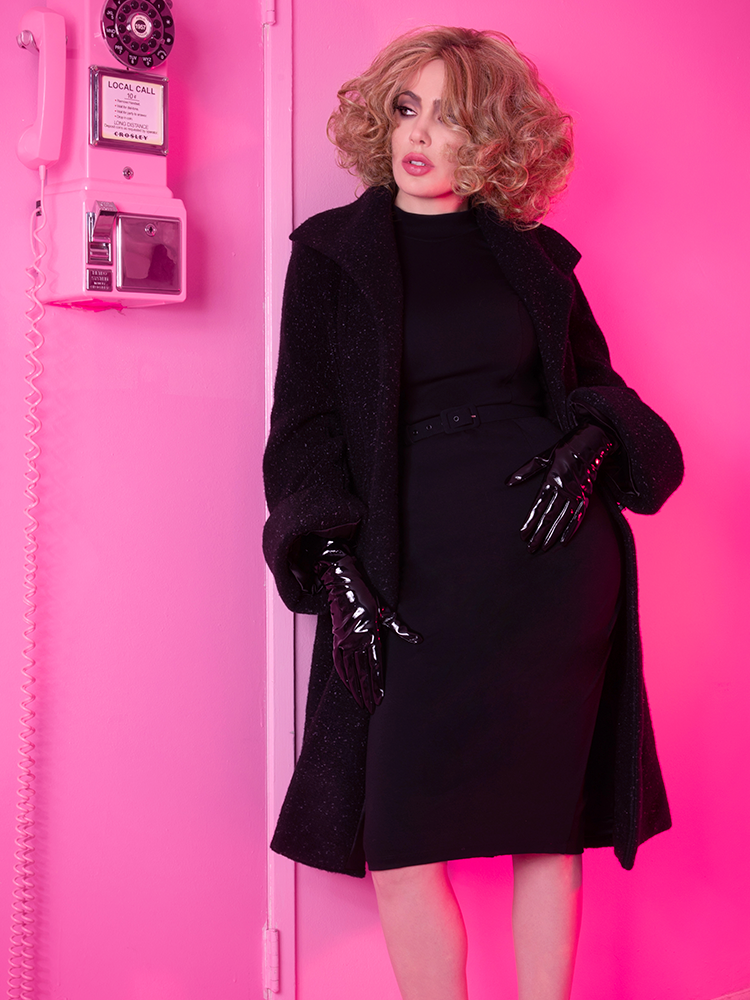 Posed next to an old rotary phone in an all pink room wearing a retro style dress paired with black vinyl gloves and long coat.