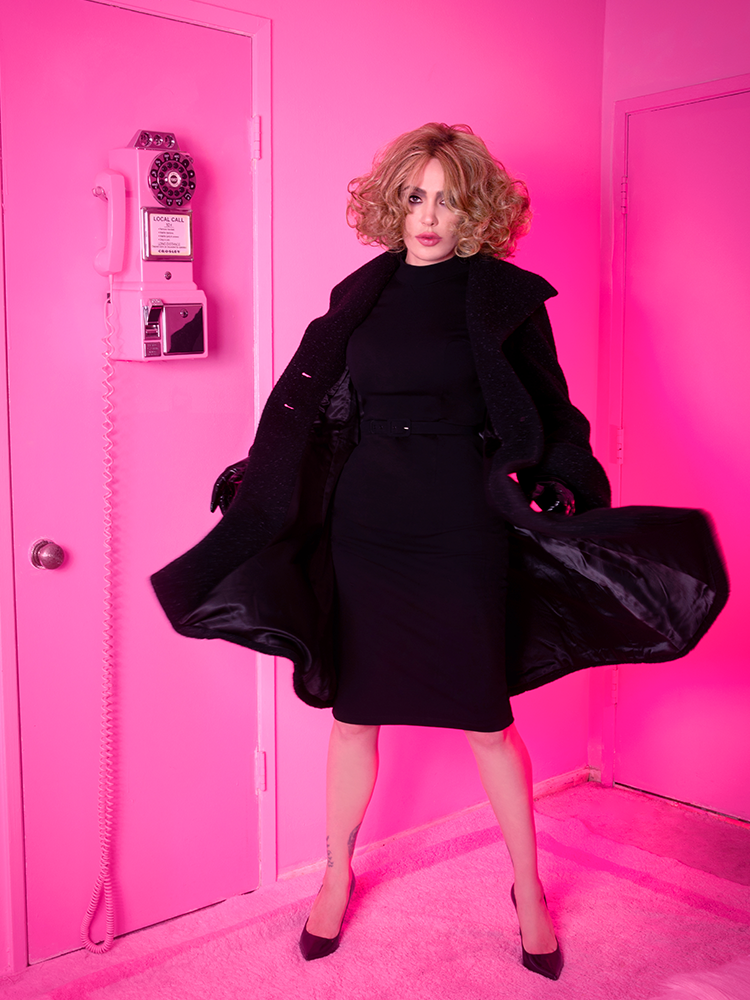 Full length shot of Micheline Pitt standing in an all pink room while wearing the Bad Girl Wiggle Dress in Black paired with a long black coat on top.