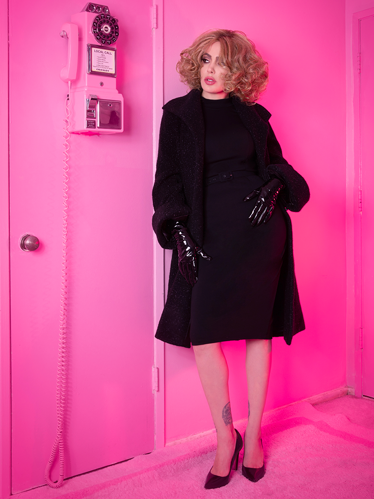 Full length shot of Micheline Pitt modeling the Bad Girl Wiggle Dress in Black while standing in an all pink room.