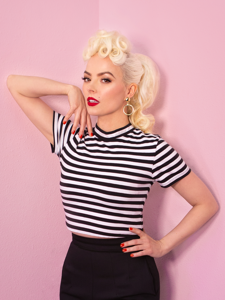 Seductively looking at the camera, Kelly Kathleen models the Bad Girl Crop Top in Black and White Stripes from vintage brand Vixen Clothing.