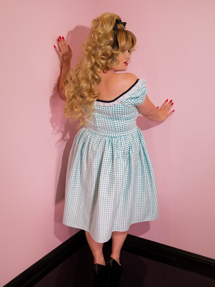 Blondie turned away from the camera to show off the back of her Bardot Beauty Dress in Blue Gingham.