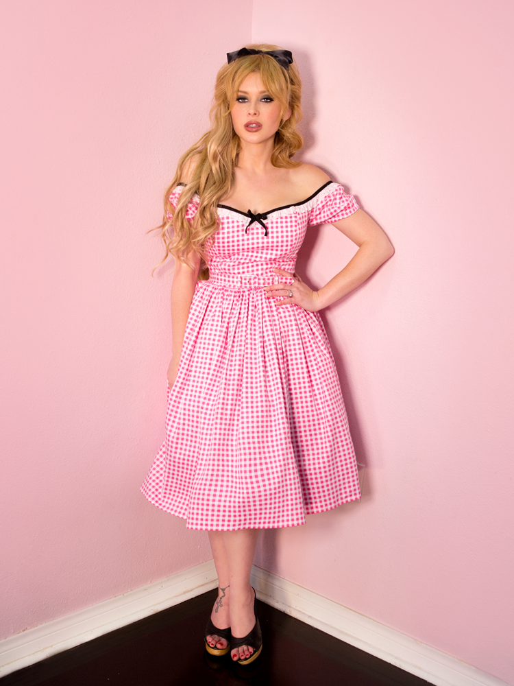 Full body shot of model standing up with her hand on her hip while wearing a pink gingham retro dress.
