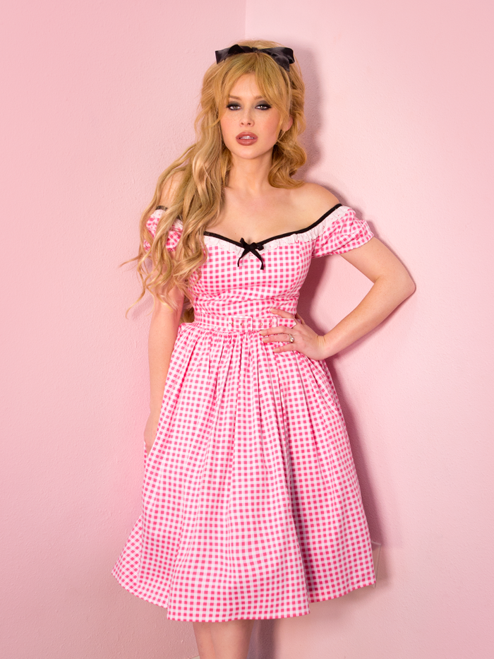 Blonde model wearing a pink gingham print dress off the shoulder. The dress also features a black bow in the center of the bust.