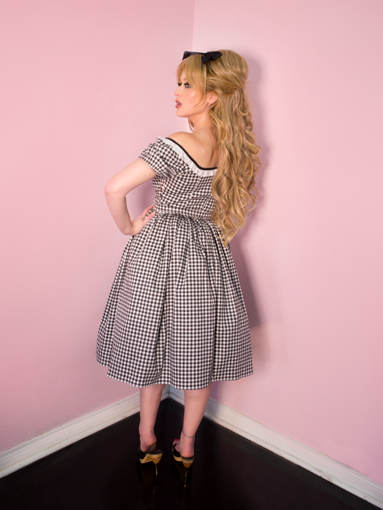 Back shot of a long haired blonde model wearing a black gingham print dress that falls just below the the knee.
