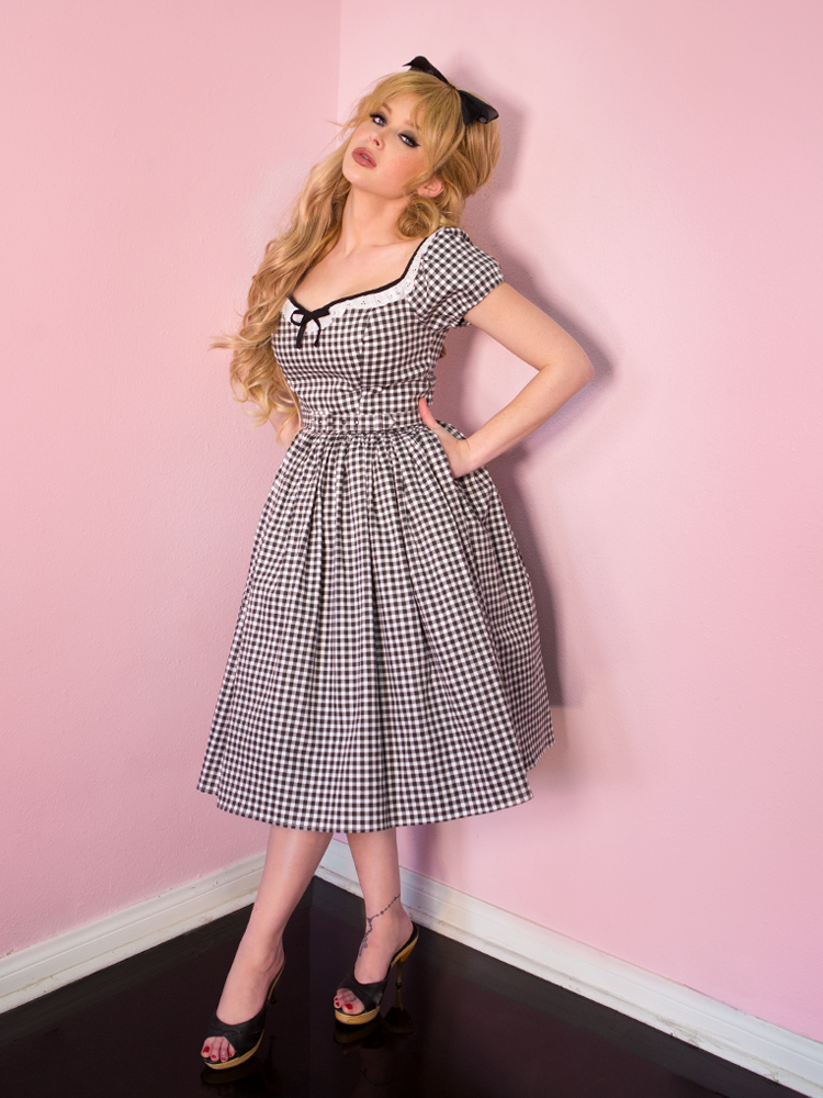 Blonde model tilting her head with her hands tucked into her pockets, wearing the Bardot Beauty Dress in Black Gingham from Vixen Clothing.