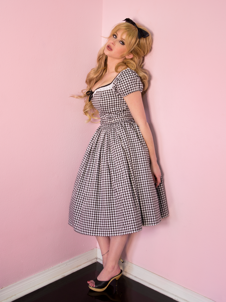 Model standing up and leaning against a pink wall while wearing a black gingham print dress from Vixen Clothing.