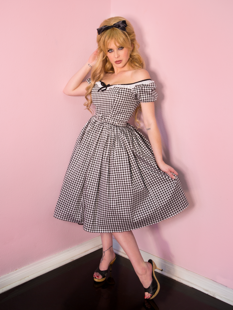 Model standing with one hand behind her head and the other pulling on her dress to show off the print, wearing a vintage inspired dress featuring a black gingham print and bow in the center of the bust area.