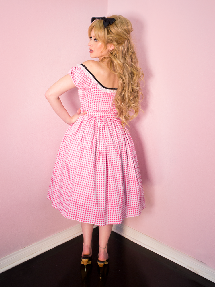 Model turned towards the wall and away from the camera, while wearing a retro style dress in pink gingham print with a partly open back.
