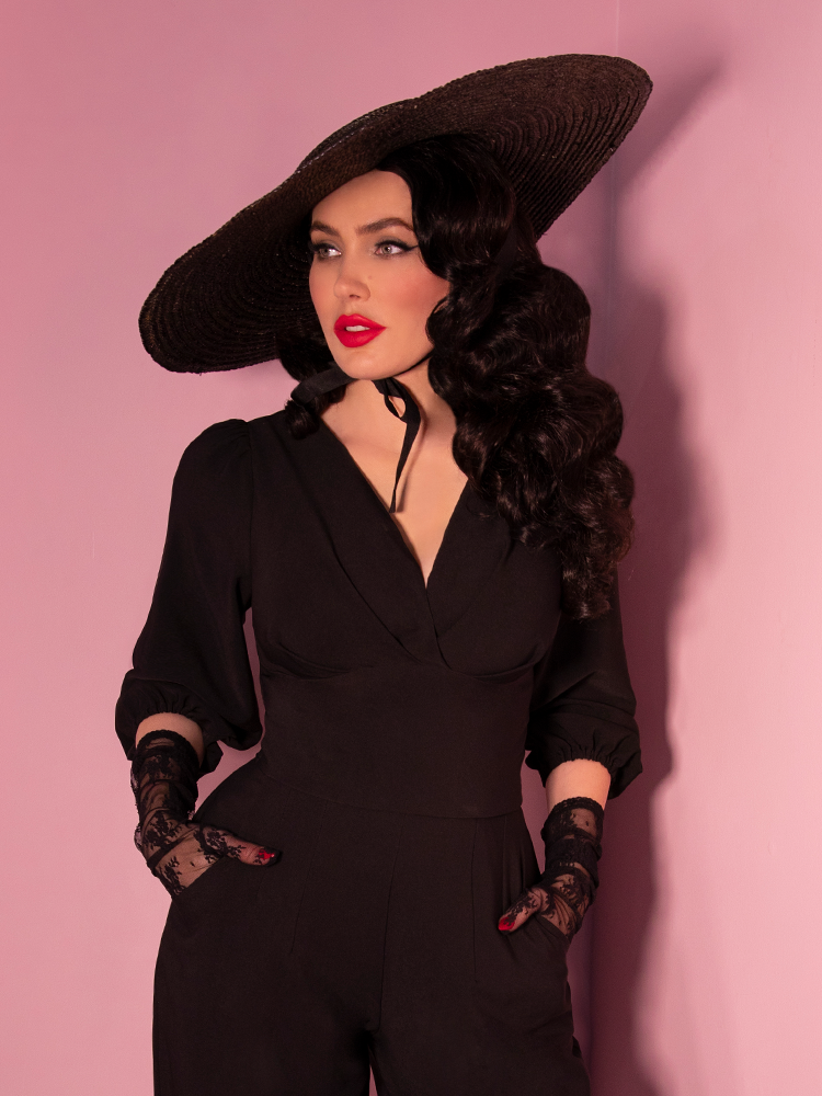Model Micheline Pitt wearing a black cropped blouse with vintage style black hat and lace gloves