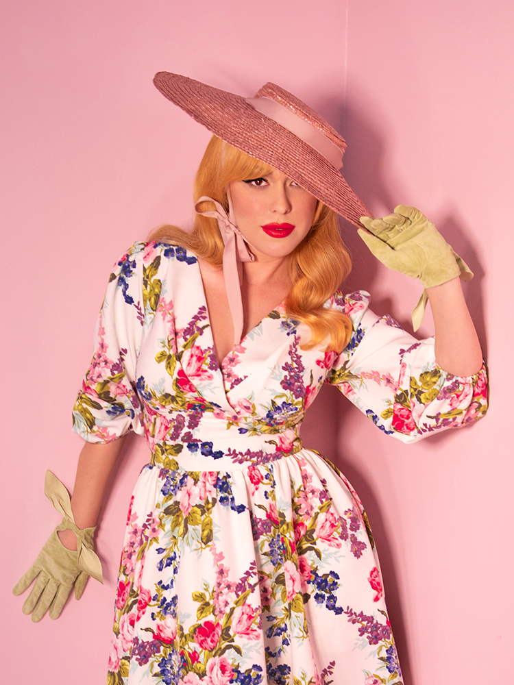 Model, holding her hat, wearing a white floral vintage blouse