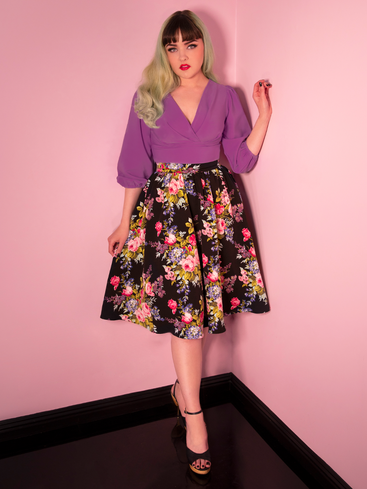 Full body shot of model wearing a cropped purple blouse and knee length floral vintage skirt.