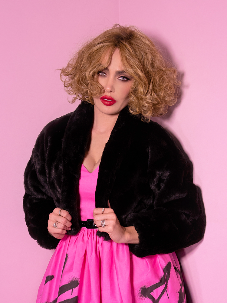 A closeup of Micheline Pitt looking at the camera modeling the cropped glam jacket in black paired with a pink and black dress.