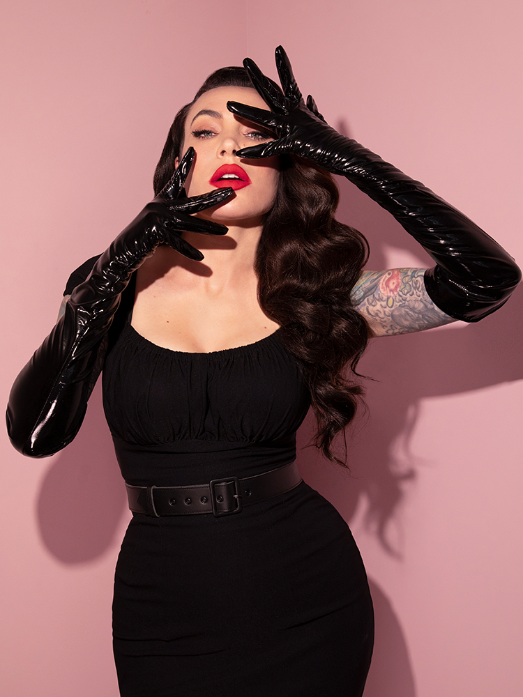 Product shot of black vinyl gloves laying on a pink floor made by retro inspired clothing company Vixen Clothing.