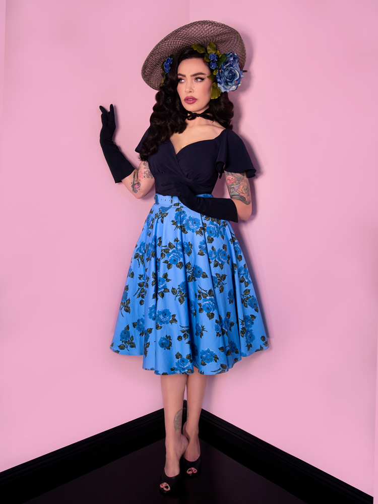 Full body shot of Micheline Pitt standing and looking off-camera while posing with her hands delicately placed in the air, is wearing the Babydoll Top in Navy from Vixen Clothing - a dark colored, loose and open retro top made for all vintage clothing lovers out there.