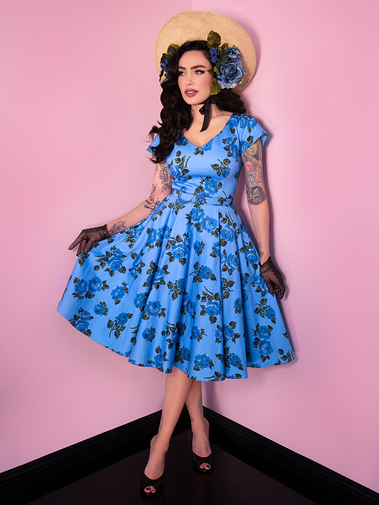 Showing off the print of her dress, Micheline Pitt sports the Vanity Fair dress in Blue Vintage Roses from Vixen Clothing.