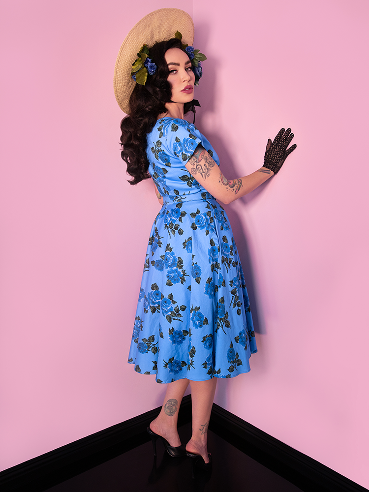 Micheline Pitt, turned away from the camera but looking over her shoulder and bracing herself against a wall, wearing a vintage inspired dress from Vixen Clothing.