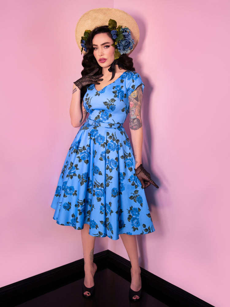 Model posing while wearing a blue vintage style dress with blue rose print.