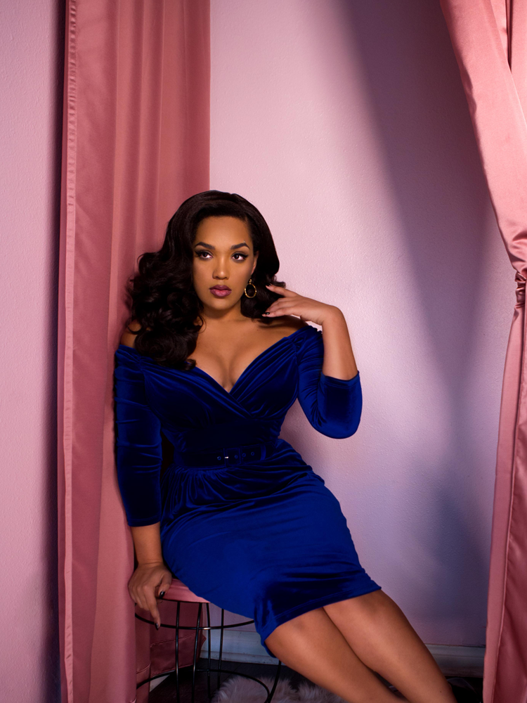 African American female model sitting down on a stool in a fitting room while showing off a blue velvet retro style dress.