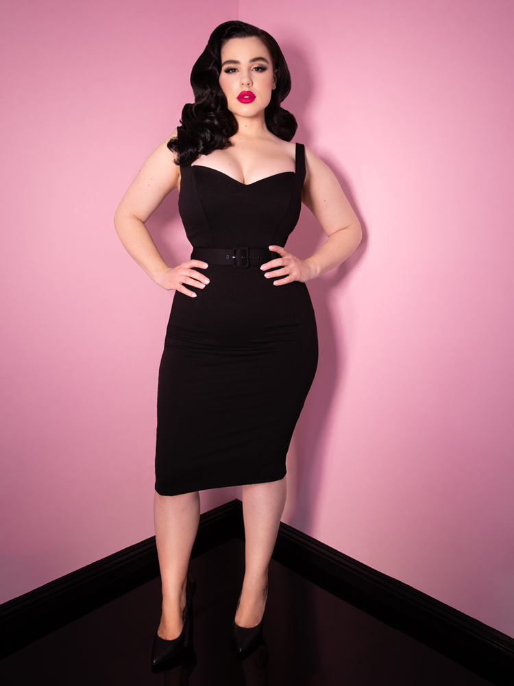 Full body shot of a jet black haired model seductively looking at the camera with her hands on her hips and wearing the Bombshell Wiggle Dress in Black. This dress is the newest retro inspired dress from Vixen Clothing.