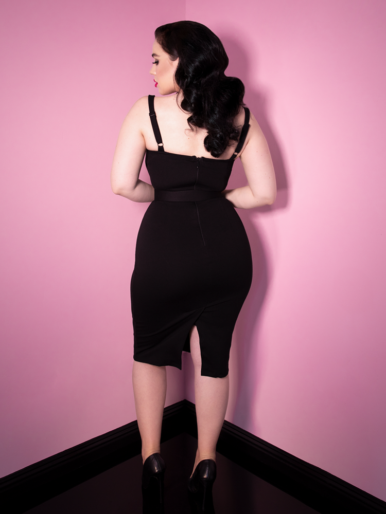Model facing the wall with her head slightly turned back towards the camera wears the newest release from Vixen Clothing; a retro inspired wiggle dress meant to accentuate your curves.