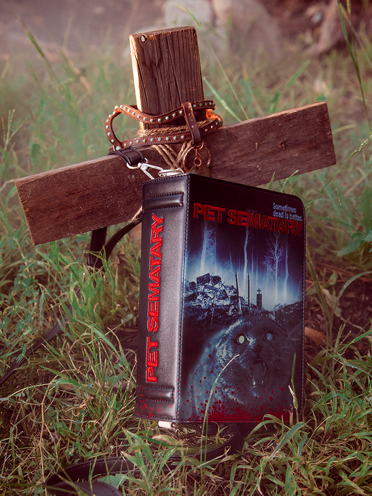 Pet Sematary book purse propped up against makeshift cross.
